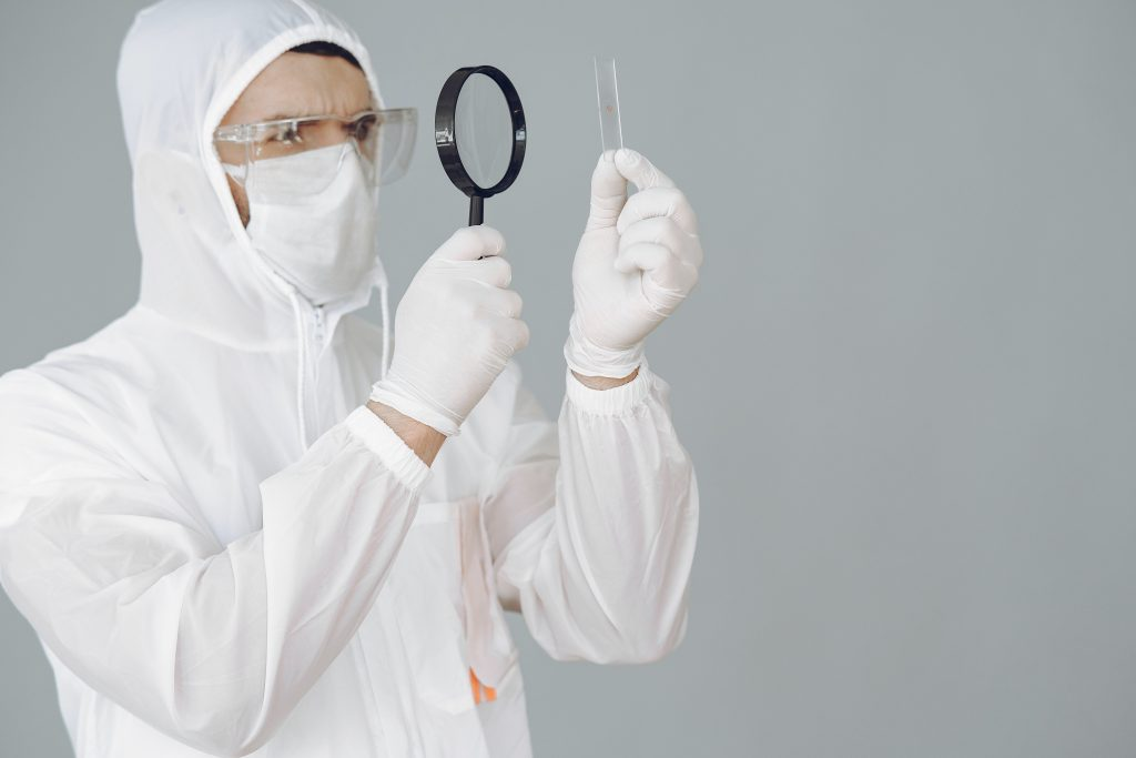 Person holding a magnifying glass to ensure consistent CBD manufacturing