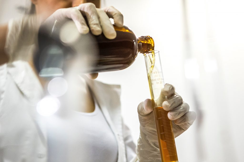 Lady wearing lab coat and gloves mixing essential oils